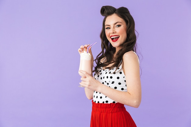 Portret pięknej pin-up girl noszącej jasny makijaż stojący na białym tle nad fioletową ścianą, pijąca koktajl mleczny