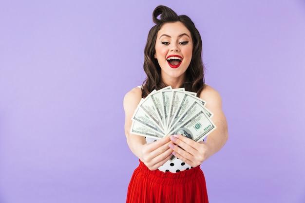 Portret pięknej pin-up girl noszącej jasny makijaż stojący na białym tle nad fioletową ścianą, pokazujący banknoty pieniędzy