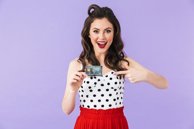 Portret pięknej pin-up girl noszącej jasny makijaż stojący na białym tle nad fioletową ścianą, pokazujący plastikową kartę kredytową