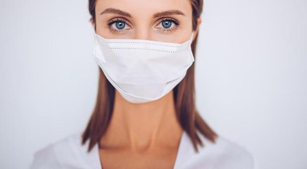 Portret pięknej potomstwo doktorska jest ubranym ochronna maska