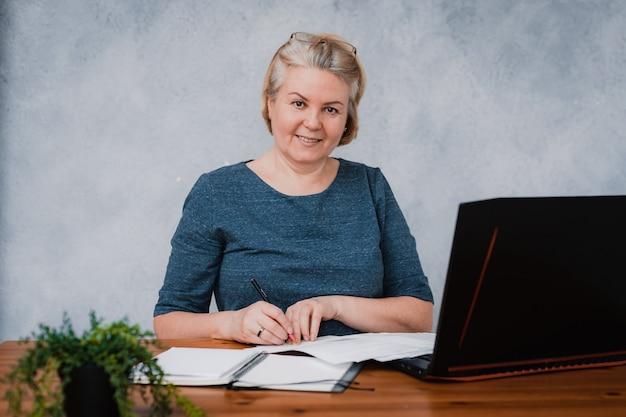 Portret pięknej pracującej poważnej biznesowej starszej kobiety z laptopem przy jej biurkiem
