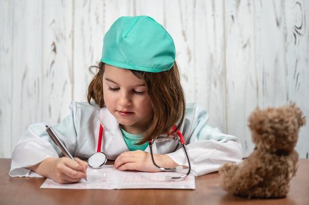 Portret pięknej przemyślanej dziewczynki odgrywającej rolę lekarza, marzącej i tworzącej pomysły w jej umyśle. proces twórczy. koncepcja edukacji i szkoły. selektywne ustawianie ostrości