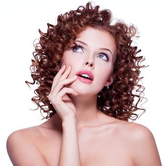 Portret pięknej, przemyślanej kobiety z kręconymi włosami, pozowanie w studio na białym tle.