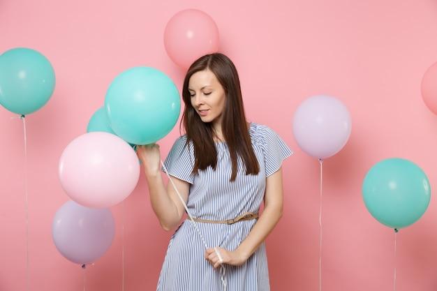 Portret pięknej przetargu młoda kobieta szczęśliwa w niebieskiej sukience trzyma kolorowe balony patrząc w dół na jasnym tle trendów różowy. urodziny wakacje, koncepcja ludzie szczere emocje.