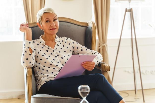 Portret pięknej psychoterapeutki w bluzce w kropki, siedzącej samotnie w swoim gabinecie