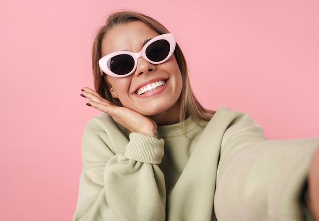 Portret pięknej radosnej kobiety w okularach przeciwsłonecznych, uśmiechającej się i biorącej selfie na różowym tle