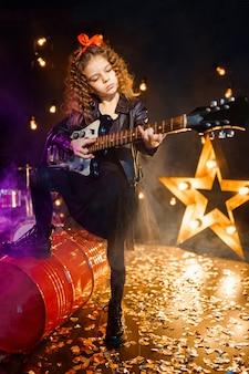 Portret pięknej rockowej dziewczyny z kręconymi włosami w skórzanej kurtce i grającej na gitarze elektrycznej