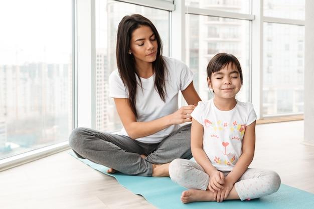 Portret pięknej rodziny matki i dziecka spędzających czas razem i uprawiających sport w domu w pobliżu dużych okien