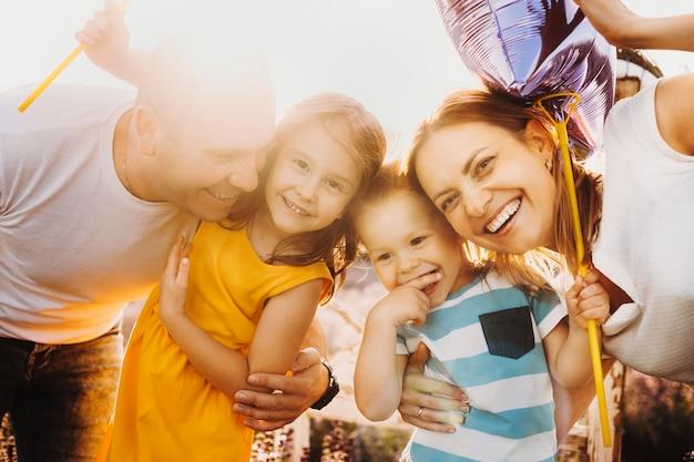 Portret pięknej rodziny obejmując przed zachodem słońca, śmiejąc się i patrząc na kamery.