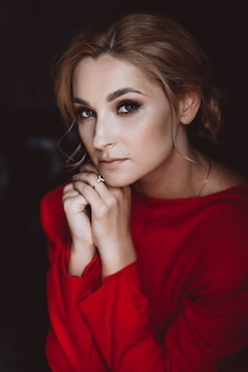 Portret pięknej romantycznej dziewczyny damy w czerwonej sukience w pokoju w stylu loftu. piękno, moda.