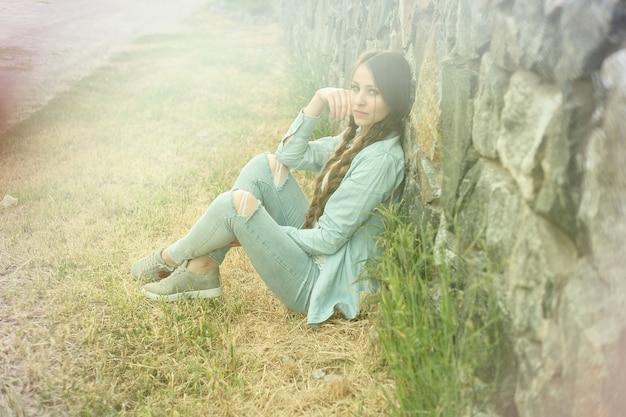 Portret pięknej romantycznej młodej kobiety na wsi o zachodzie słońca. atrakcyjna dziewczyna w dżinsowych ubraniach