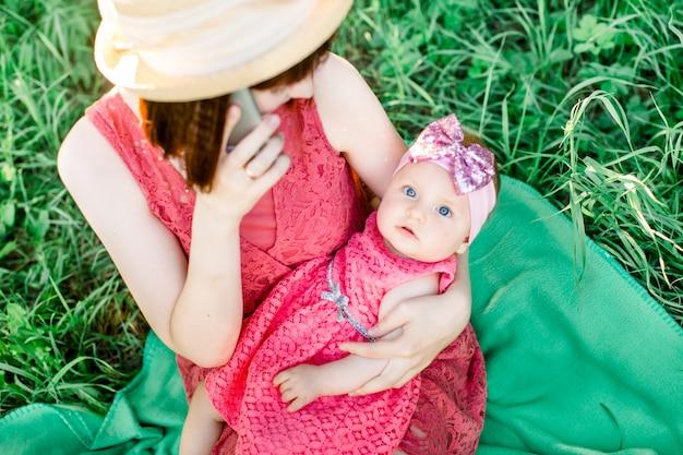 Portret pięknej, roześmianej dziewczyny o cudownych niebieskich oczach trzymanej przez matkę na plecach na kolanach w ogrodzie
