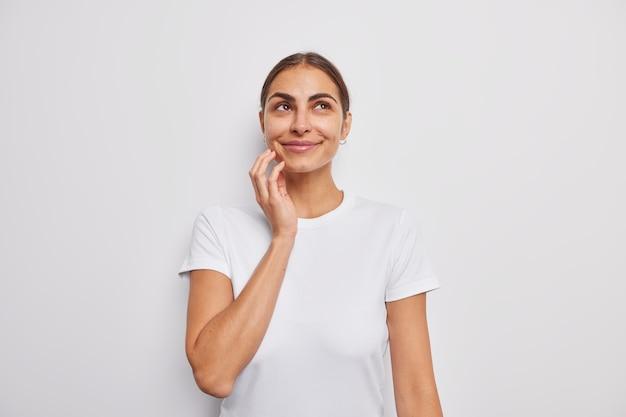 Portret pięknej, rozmarzonej kobiety o ciemnych włosach, uśmiecha się delikatnie nad głową, przywołuje miłe wspomnienia ubrane w luźną koszulkę na białym tle nad białą ścianą ma romantyczne myśli stoi w pomieszczeniu