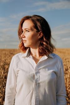 Portret pięknej rudowłosej dziewczyny w białej koszuli. stoi na polu żyta w słoneczny dzień. spokojny wyraz twarzy. pojęcie ustępstw. zdjęcie pionowe
