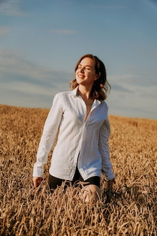 Portret pięknej rudowłosej dziewczyny w białej koszuli. stoi na polu żyta w słoneczny dzień. spokojny wyraz twarzy. pojęcie ustępstw