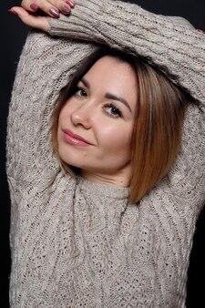Portret pięknej rudowłosej kobiety w szarym melanżowym swetrze z włosami