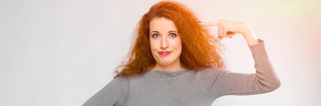 Portret pięknej rudzielec szczęśliwa uśmiechnięta młoda kobieta w szarość ubraniach pokazuje śmiesznego gest na szarym tle