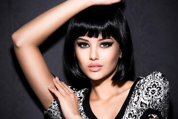 Portret pięknej seksownej kobiety z jasny makijaż pozowanie na szarym tle