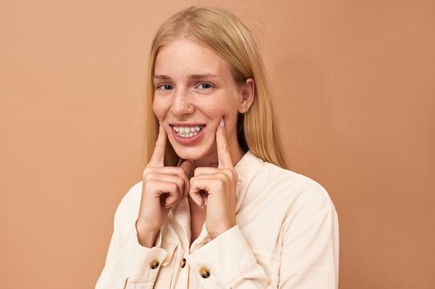 Portret pięknej sfrustrowanej młodej kobiety z długimi jasnymi włosami i kolczykiem w nosie z bolesnym wyrazem twarzy, podczas gdy jej dziąsła bolą z powodu ciasnych aparatów ortodontycznych
