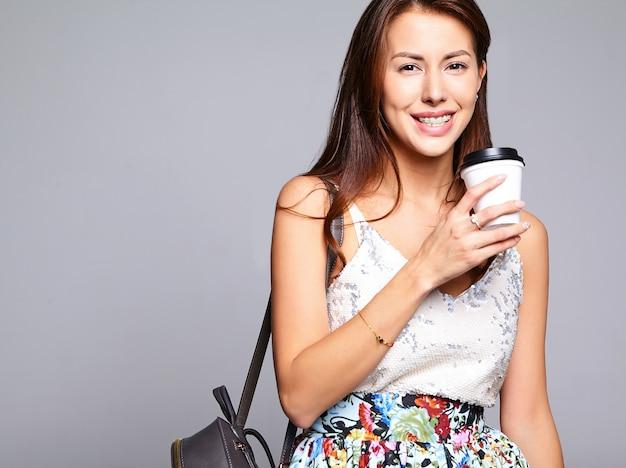 Portret pięknej ślicznej brunetki kobiety model w nawiasy klamrowe i przypadkowe lato ubrania bez makijażu odizolowywającego na popielatym. picie świeżej kawy