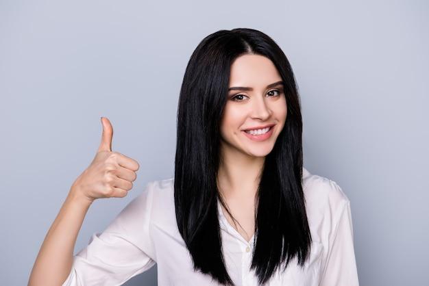 Portret pięknej ślicznej młodej kobiety z zębatym uśmiechem i czarnymi włosami pokazując kciuk znak palcami