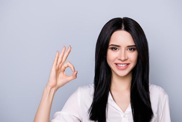 Portret pięknej ślicznej młodej kobiety z zębatym uśmiechem i czarnymi włosami pokazuje ok znak palcami