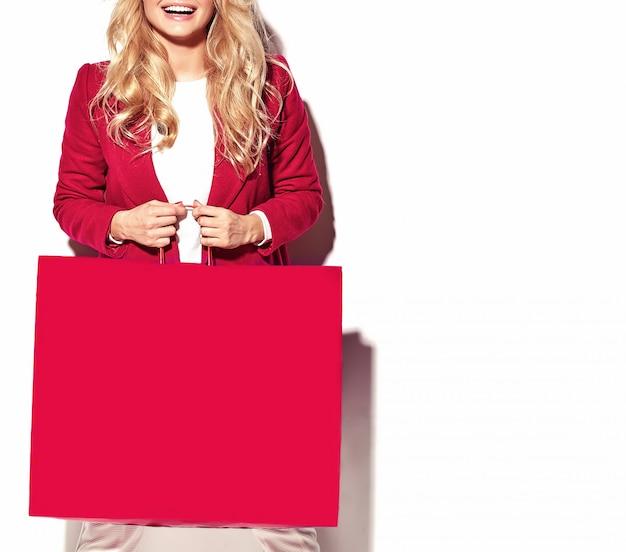 Portret pięknej ślicznej szczęśliwej słodkiej zdziwionej blondynki kobiety dziewczyny mienia w jej rękach duża torba na zakupy w modniś czerwieni ubraniach odizolowywających na bielu