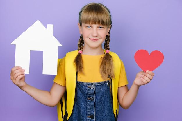 Portret pięknej ślicznej uśmiechniętej uczennicy trzymającej małe czerwone serce i papierowy model białego domu, szczęśliwy patrząc na kamerę, nosi żółty plecak, na białym tle nad pastelowym fioletowym tle w studio