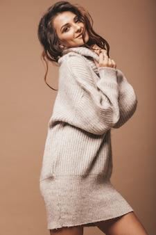 Portret pięknej słodkiej słodkie uśmiechnięta brunetka kobieta. dziewczyna w swobodnym szarym swetrze. model stwarzające w studio