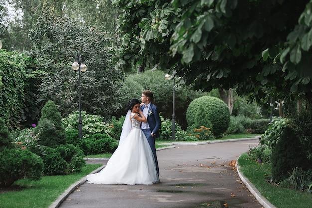 Portret pięknej ślub pary na spacerze w zielonym parku