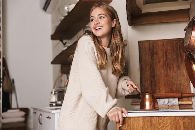 Portret pięknej śmiesznej kobiety noszącej zwykłe ubrania, uśmiechającej się i robiącej kawę w cezve w przytulnej kuchni