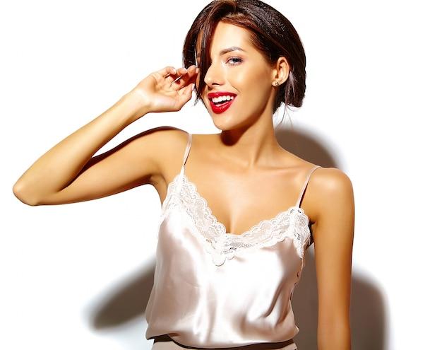 Portret pięknej śmiesznej uśmiechniętej brunetki kobiety dziewczyny wariuje przypadkowe lato ubrania na białym tle