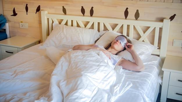Portret pięknej śpiącej kobiety leżącej w koralikach noszącej maskę na oczy