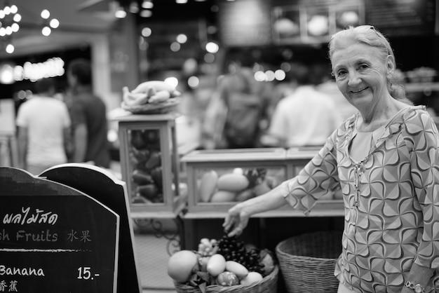 Portret pięknej starszej kobiety relaksującej się po mieście bangkok w czerni i bieli