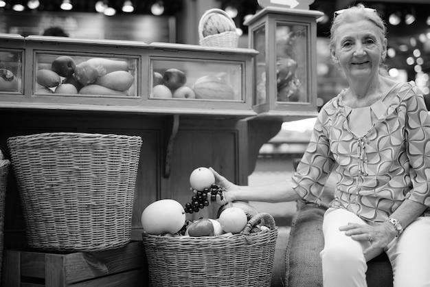 Portret pięknej starszej kobiety turystycznej relaksującej się po mieście bangkok w czerni i bieli