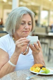 Portret pięknej starszej kobiety w kawiarni