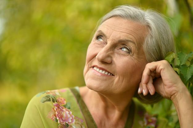 Portret pięknej starszej kobiety w zielonym parku