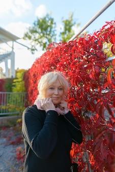 Portret pięknej starszej kobiety z krótkimi blond włosami relaks w parku na świeżym powietrzu jesienią