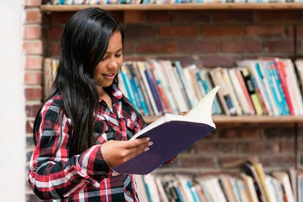 Portret pięknej studenckiej dziewczyny w bibliotece. biedna koncepcja niemowlęcia