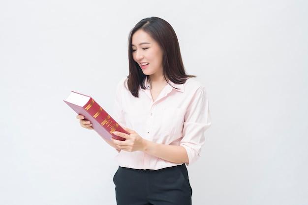 Portret pięknej studentki w różowej koszuli trzyma książkę na białym tle nad białym tle studio