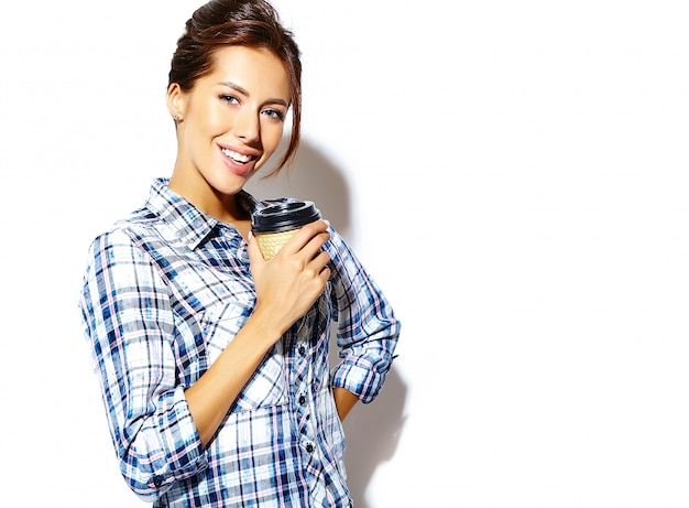 Portret pięknej stylowej fajne nastolatka w kraciaste koszule, trzymając plastikowy kubek kawy. miejsce dostępne.