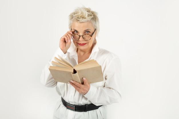 Portret pięknej stylowej kobiety w okularach z książką