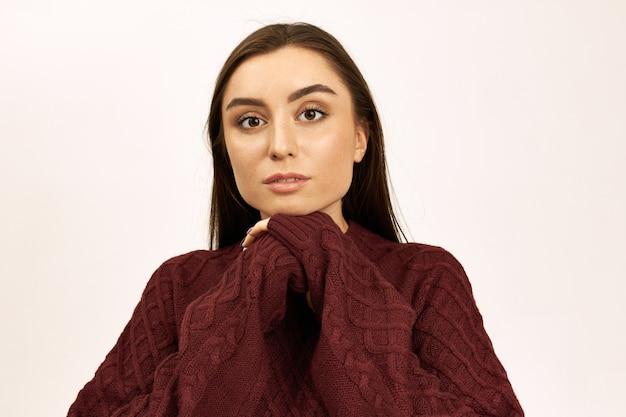 Portret pięknej stylowej młodej kobiety o brązowych oczach i prostych włosach, pozowanie na białym tle z rękami splecionymi w swetrze z długimi rękawami oversize, będąc zimnym w zimowy dzień. sezon i odzież