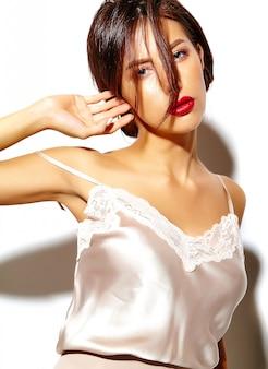 Portret pięknej szczęśliwa śliczna seksowna brunetki kobieta z czerwonymi wargami w piżamy bieliźnie na białym tle