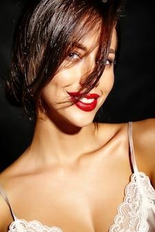 Portret pięknej szczęśliwa śliczna seksowna brunetki kobieta z czerwonymi wargami w piżamy bieliźnie na czarnym tle
