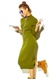 Portret pięknej szczęśliwa śliczna uśmiechnięta brunetki kobiety dziewczyna w przypadkowych zielonych modnisiów lata ubraniach odizolowywających na bielu w okularach przeciwsłonecznych słucha muzykę w smartphone z hełmofonami