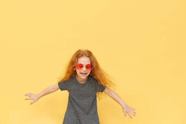 Portret pięknej szczęśliwej dziewczynki w modnych odcieniach i sukience, trzymając szeroko rozstawione ramiona i śmiejąc się