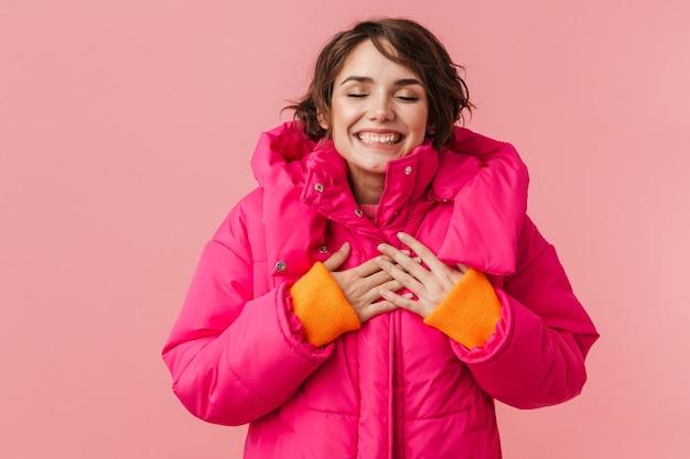 Portret pięknej szczęśliwej kobiety w ciepłym płaszczu, uśmiechniętej i trzymającej się za ręce na klatce piersiowej odizolowanej na różowo
