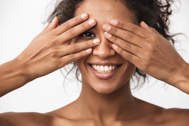 Portret pięknej szczęśliwej młodej kobiety afrykańskiej pozowanie na białym tle nad białą ścianą obejmującą oczy rękami.