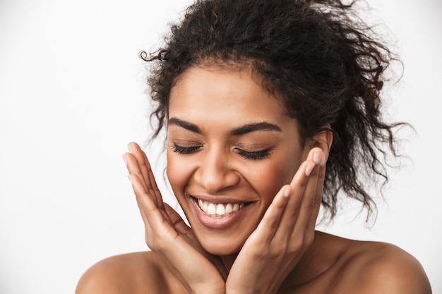 Portret pięknej szczęśliwej młodej kobiety afrykańskiej pozowanie na białym tle nad białą ścianą.